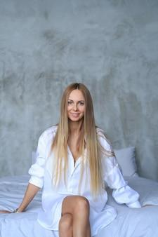 Mooie jonge vrouw poseren in het bed