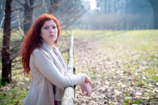 Mooie jonge vrouw poseren in het park