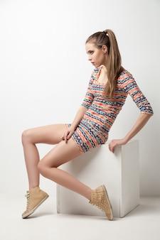 Mooie jonge vrouw poseren in jurk op kubus. mode foto