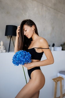 Mooie jonge vrouw poseren in lingerie in de woonkamer