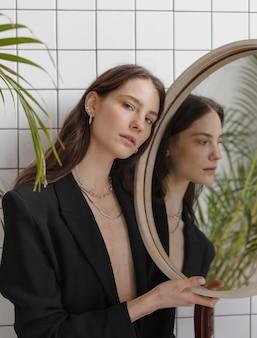 Mooie jonge vrouw poseren in spiegel