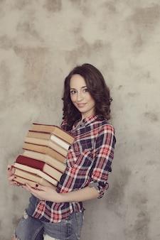 Mooie jonge vrouw poseren met boeken