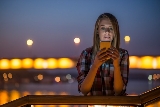 Mooie jonge vrouw praten over de mobiele telefoon in de nacht stad.