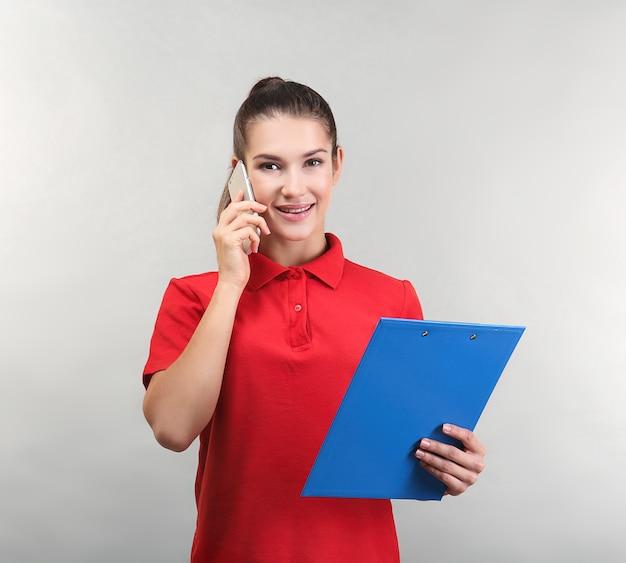 Mooie jonge vrouw praten via de mobiele telefoon terwijl u klembord vasthoudt