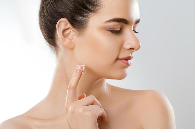 Mooie jonge vrouw raakt eigen gezicht aan. cosmetologie, schoonheid en spa.