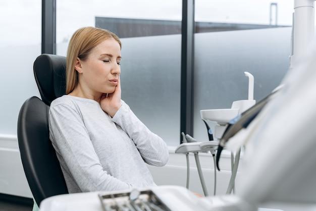 Mooie, jonge vrouw raakt haar wang aan met haar hand en huivert bij de kiespijn. een vrouw in een tandartsstoel huivert van de pijn