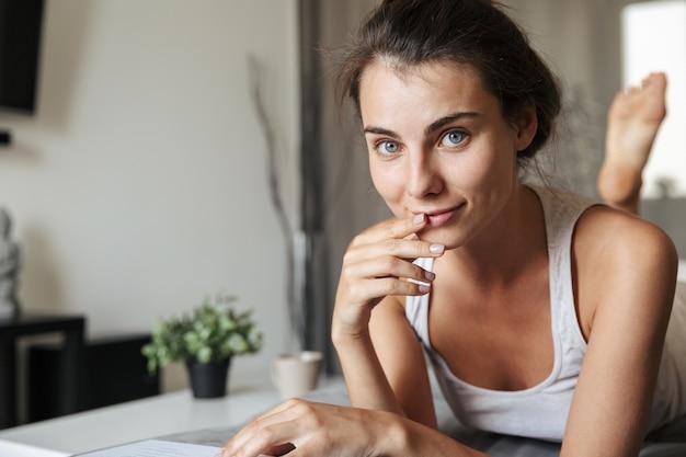 Mooie jonge vrouw realxing op een bank thuis, lezen, groene appel eten
