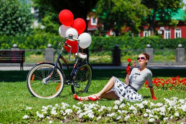Mooie jonge vrouw retro pin-up stijl met fiets