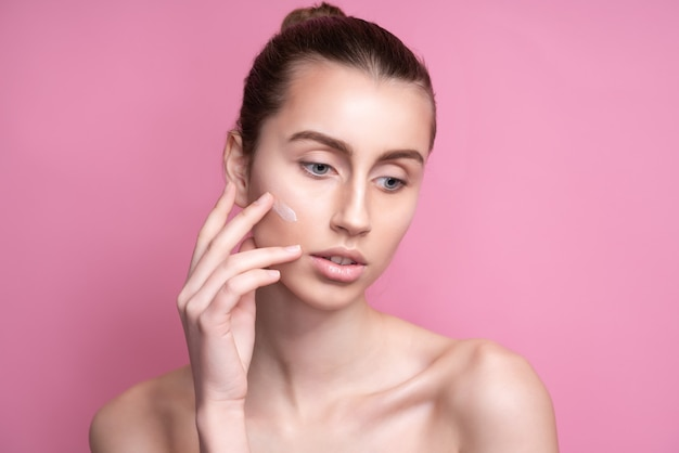 Mooie jonge vrouw room toe te passen op haar gezicht op roze