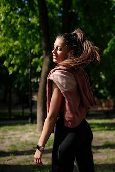 Mooie jonge vrouw rust na het joggen in het park.
