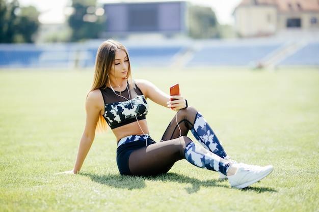 Mooie jonge vrouw rust op het veld luisteren naar muziek