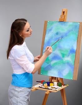 Mooie jonge vrouw schilder op het werk, op een grijze achtergrond