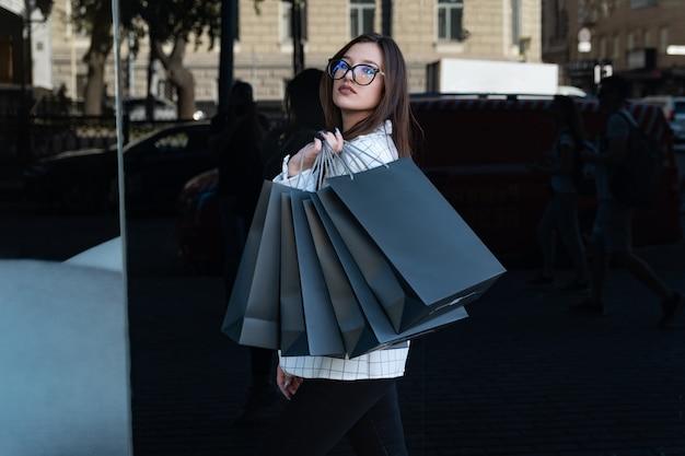 Mooie jonge vrouw shopper boodschappentassen in handen te houden. stijlvol meisje in glazen. black friday, verkoop, korting.