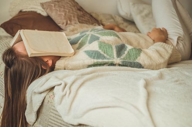 Mooie jonge vrouw slapen op bed met boek dat haar gezicht bedekt, omdat het lezen van boek met het voorbereiden van examen van de universiteit, vrouw slaperig met moe zodat vrije tijd, ontspanning en onderwijs concept.