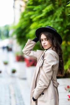Mooie jonge vrouw slijtage in hoed en jas wandelen in de stad.