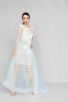 Mooie jonge vrouw speelt met zoom van transparante bleke tule jurk met kant