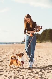 Mooie jonge vrouw spelen met corgi puppy wandelen langs oceaan strand. wijfje dat aan hond kijkt