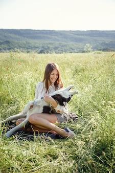Mooie jonge vrouw spelen met grappige husky hond buiten in het park