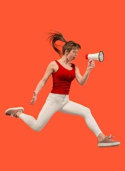 Mooie jonge vrouw springen met megafoon geïsoleerd dan rood
