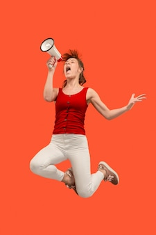 Mooie jonge vrouw springen met megafoon geïsoleerd dan rood.