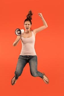 Mooie jonge vrouw springen met megafoon geïsoleerd op rode achtergrond. runnin meisje in beweging of beweging. menselijke emoties en gezichtsuitdrukkingen concept