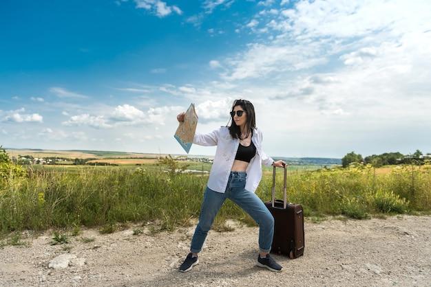 Mooie jonge vrouw staan en kijken naar de kaart op de weg, geniet van de zomervakantie in de natuur
