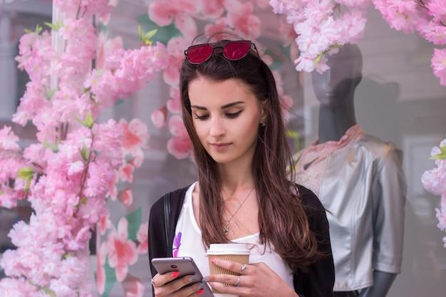 Mooie jonge vrouw staat in de buurt van een winkel, houdt de koffie en staart naar de telefoon