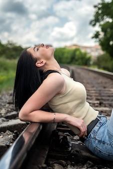 Mooie jonge vrouw staat in de buurt van het spoor, zomerse levensstijl
