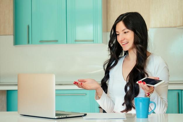Mooie jonge vrouw student (freelancer) in een witte jurk en zwart haar thuis werken met een laptop in een kleur keuken. het concept van communicatie in sociale netwerken met een telefoon in de hand