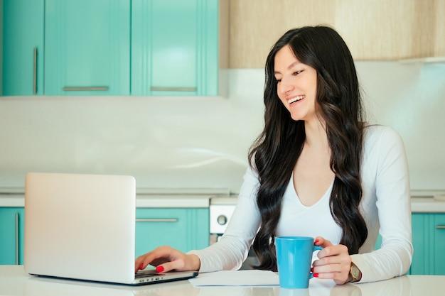 Mooie jonge vrouw student (freelancer) in een witte jurk en zwart haar thuis werken met een laptop in een turquoise kleur keuken. in de handen van een kopje, het idee van geluk