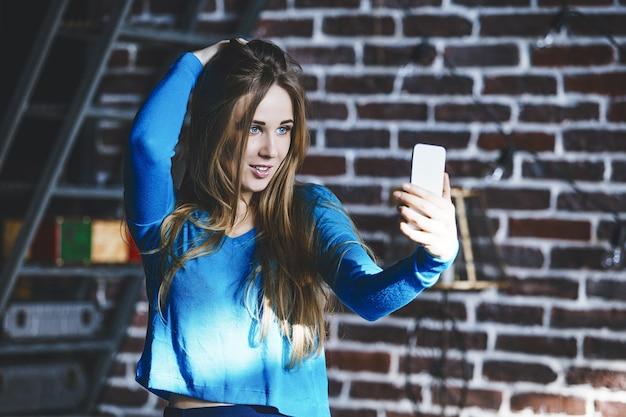 Mooie jonge vrouw succesvol modieus en mooi met mobiele telefoon in de hand