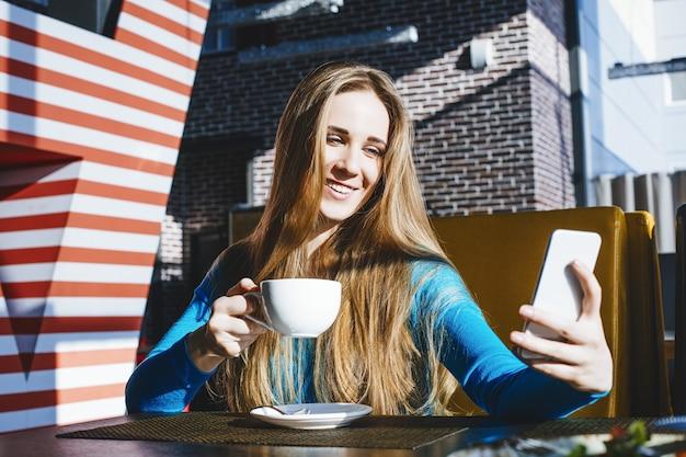 Mooie jonge vrouw succesvolle mode en mooi met een mobiele telefoon en een kopje koffie in een café