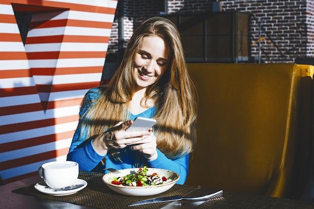 Mooie jonge vrouw succesvolle modieuze en mooie mobiele telefoon en een kom salade in het restaurant