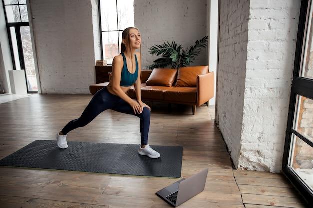 Mooie jonge vrouw thuis yoga beoefenen met laptop. online training concept