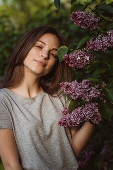 Mooie jonge vrouw, tienermeisje, dichtbij een lila struik in een zonnig lentepark. zachte selectieve focus.