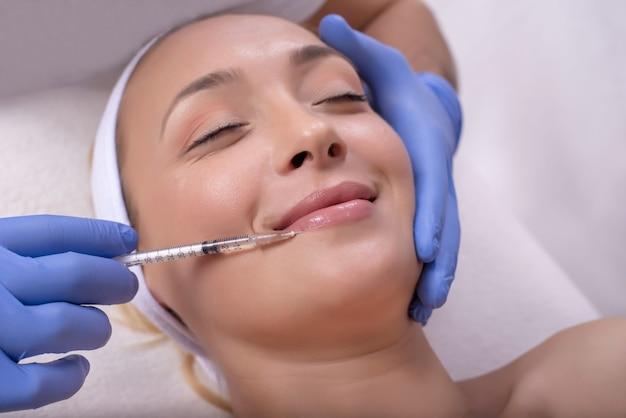 Mooie jonge vrouw tijdens huidbehandeling met hyaluronzuur in een schoonheidskliniek