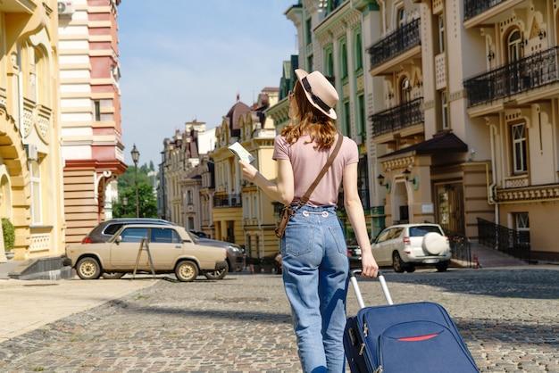 Mooie jonge vrouw toeristische aangenaam met plattegrond van de stad en koffer in het stadscentrum.
