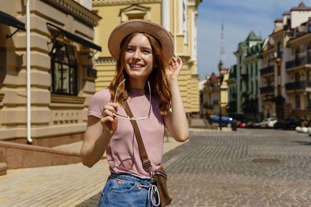 Mooie jonge vrouw toeristische aangename wandeling in het stadscentrum.