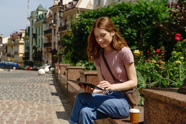 Mooie jonge vrouw toeristische met meeneem koffie in het centrum van de stad met behulp van tablet pc.