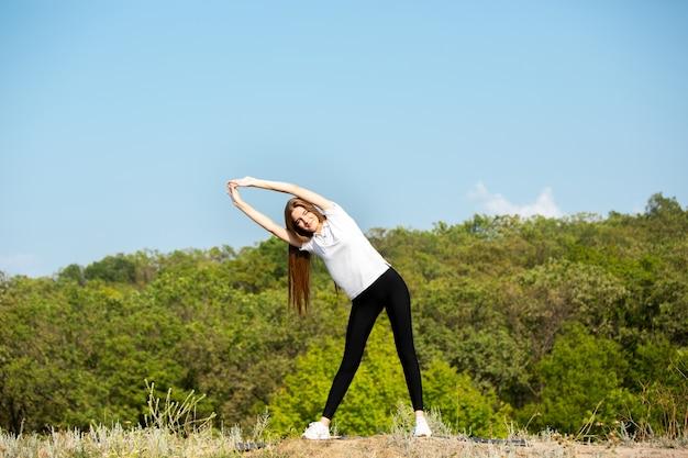 Mooie jonge vrouw training flexibiliteit buitenshuis