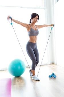 Mooie jonge vrouw training met linten thuis.