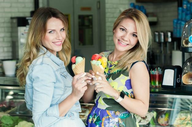 Mooie jonge vrouw twee die een italiaans roomijs eet