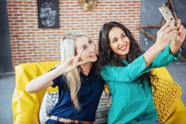 Mooie jonge vrouw twee die selfie in een koffie doen, beste vriendenmeisjes die samen pret hebben, die emotionele levensstijlmensen stellen