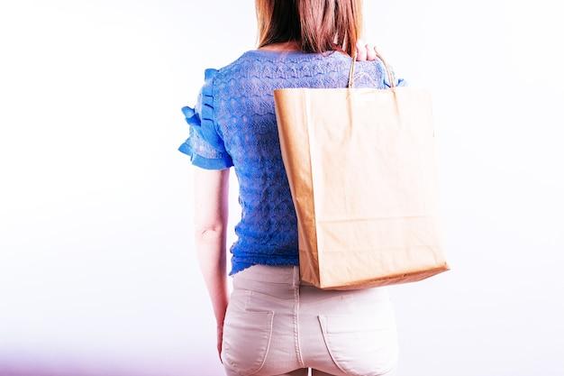 Mooie jonge vrouw van achteren met een papieren zak achter haar rug. duurzaam winkelconcept. plastic vrij
