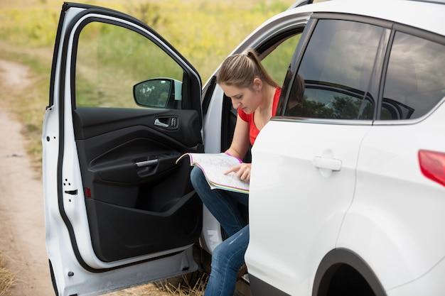 Mooie jonge vrouw verdwaalde tijdens het autorijden op het platteland