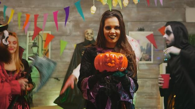Mooie jonge vrouw verkleed als een enge heks met een pompoen op een halloween-feest met haar vrienden.