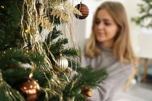 Mooie jonge vrouw versieren van een kerstboom - zachte kleuren. onscherpe achtergrond