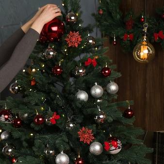 Mooie jonge vrouw versiert een kerstboom met ballen in het interieur van het nieuwe jaar. - afbeelding