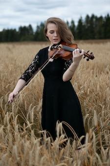 Mooie jonge vrouw viool spelen in een tarweveld