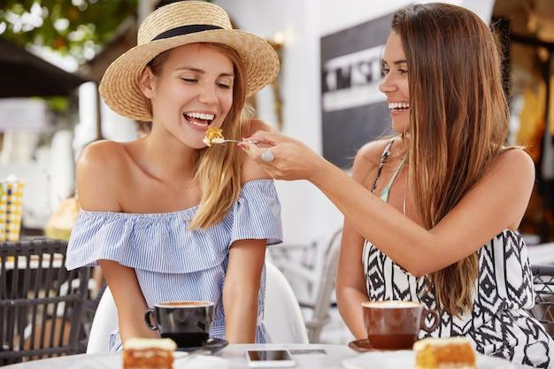 Mooie jonge vrouw voedt haar lieftallige vriendin met een stuk heerlijke cake, veel plezier samen en drink warme koffie of latte, kom naar het buitenrestaurant om te pauzeren, geniet samen van een goede nachtrust.